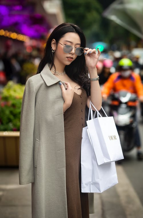 Woman In A Coat Holding White Paper Bag