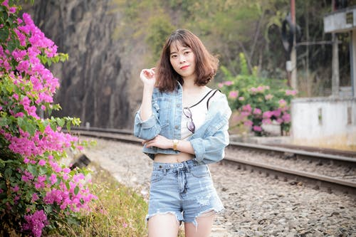 Woman In Blue Denim Shorts And White Long Sleeve Shirt Standing On Side Of Railroad