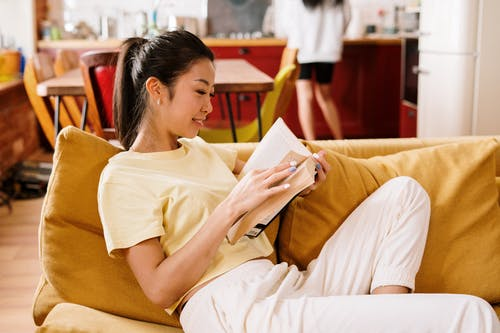 Woman in Yellow Shirt Reading Book