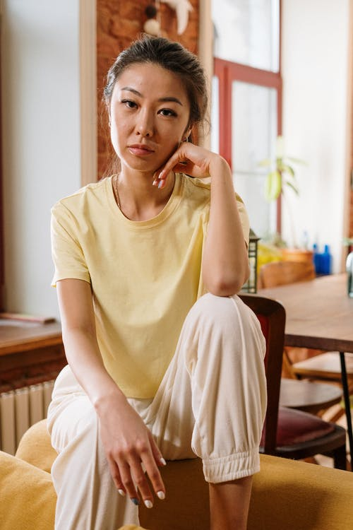 Woman in Yellow Crew Neck T-shirt Sitting on Brown Wooden Chair
