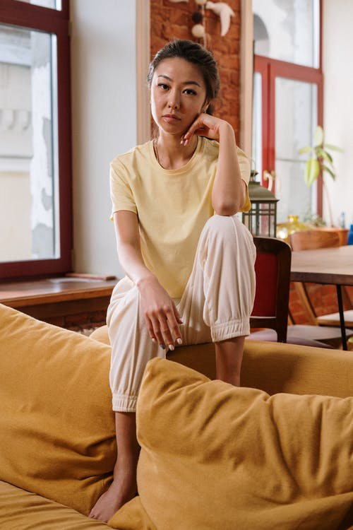 Woman in White Crew Neck T-shirt Sitting on Brown Wooden Chair