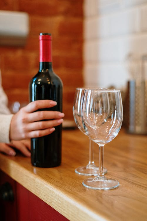 Person Holding Bottle Pouring Wine on Clear Wine Glass
