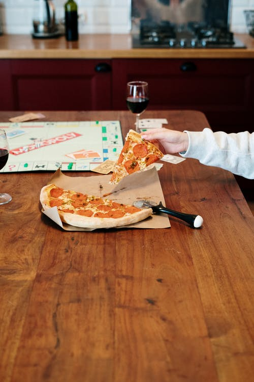 Person in White Long Sleeve Shirt Slicing Pizza