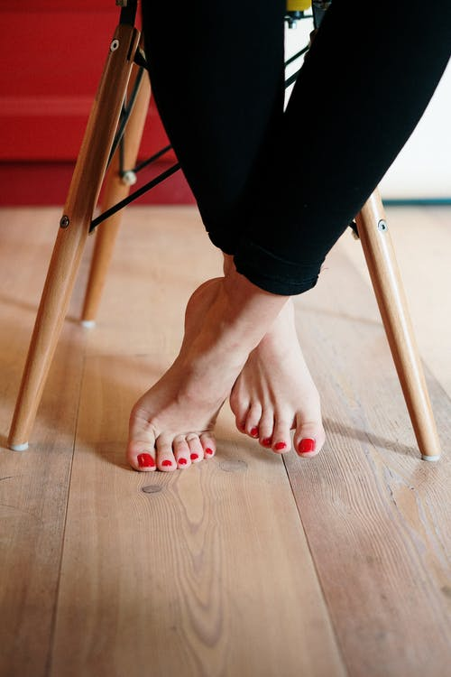 Person With Red Pedicure Standing on Brown Wooden Floor
