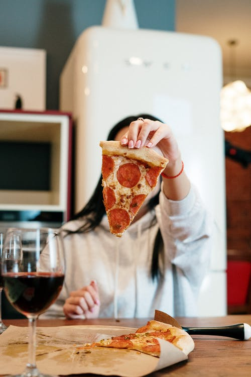 Person Holding Sliced of Pizza