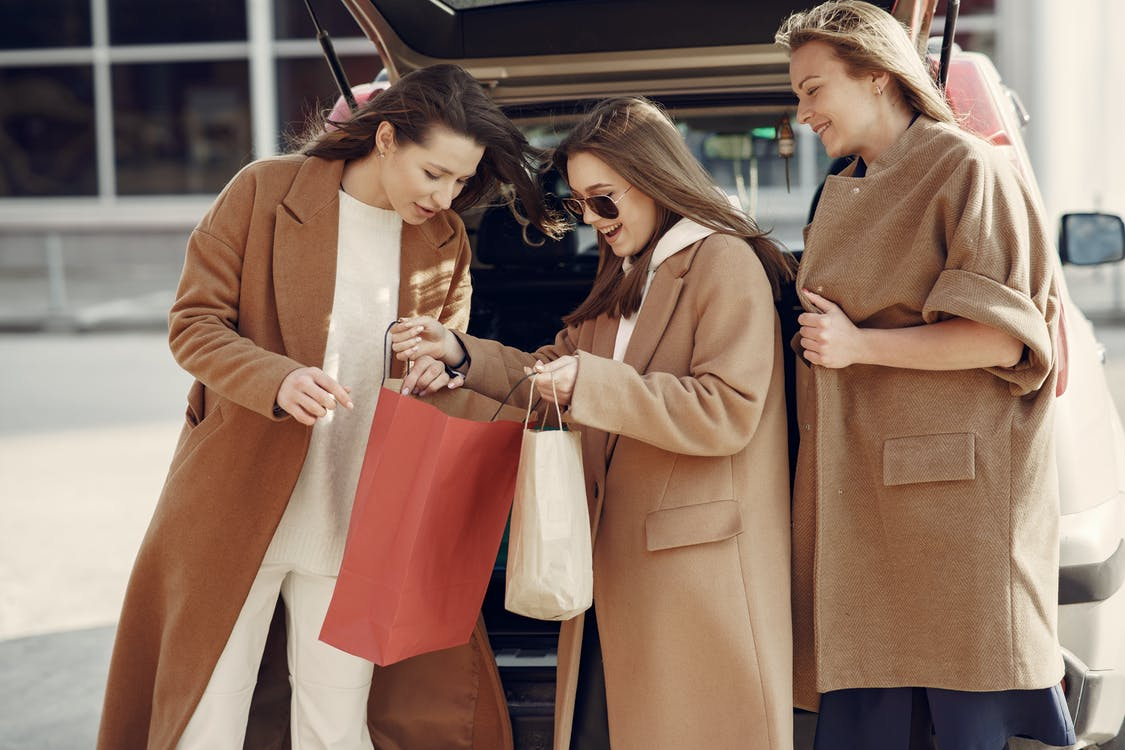 Cheerful women in elegant coats standing on parking near car and showing off by results of shopping