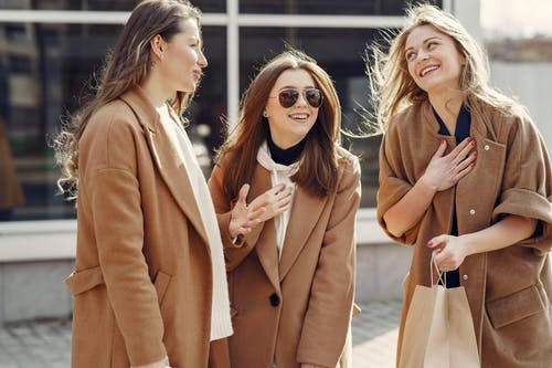 Cheerful female friends with long hair in elegant coats smiling while happily chatting with each other on street