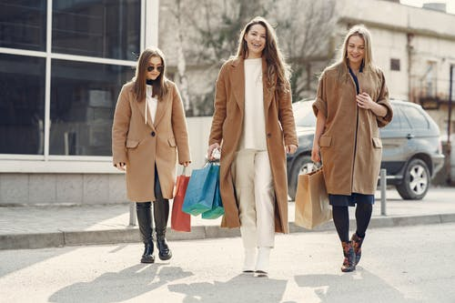 Happy women walking with paper bags after shopping