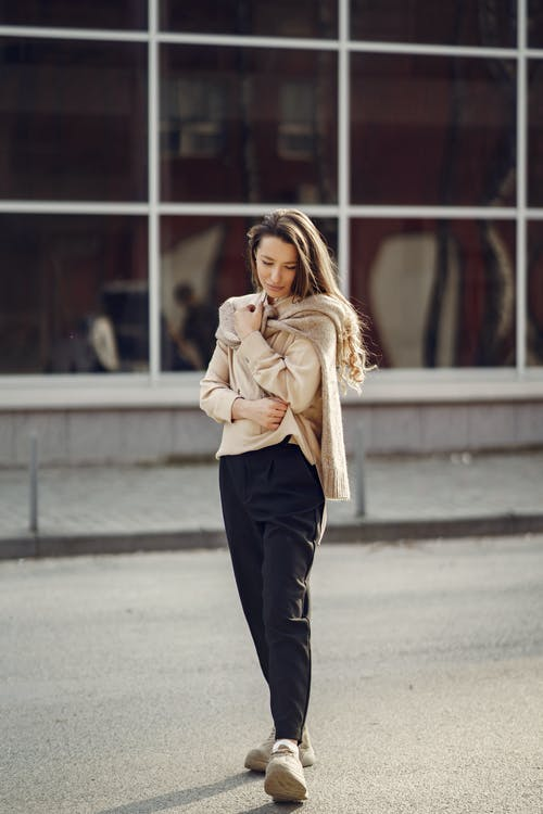 Woman in Beige Coat and Black Pants Standing on Road