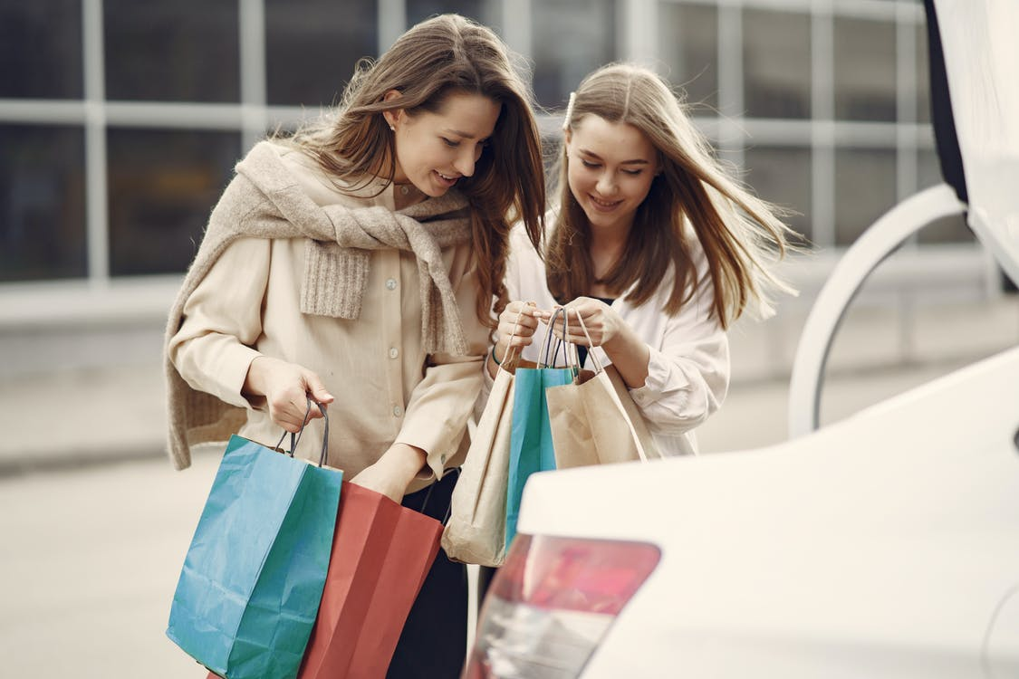 Happy women reviewing purchases of each other