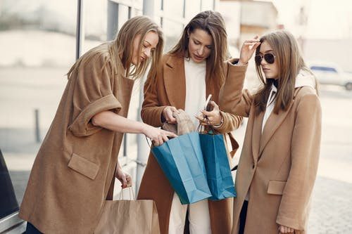 Stylish women examining new sweater in shopping bag