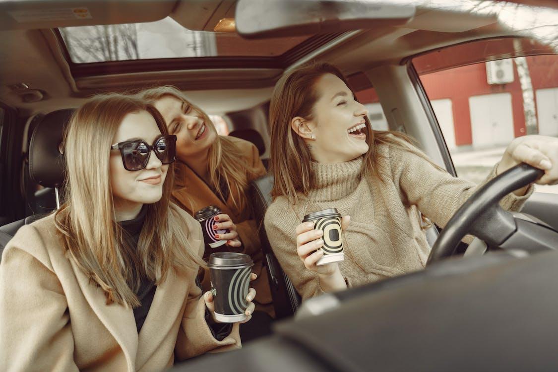Positive women driving around city street