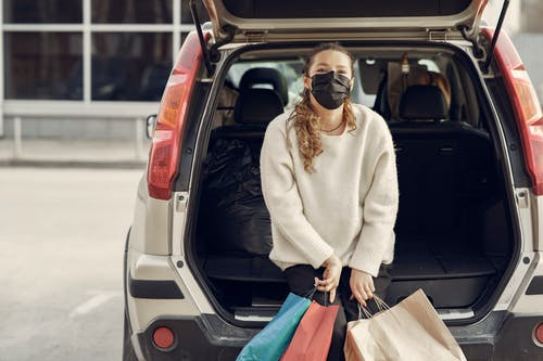 Young woman in casual clothes and protective mask sitting in trunk of modern car holding shopping bags with purchases on city street