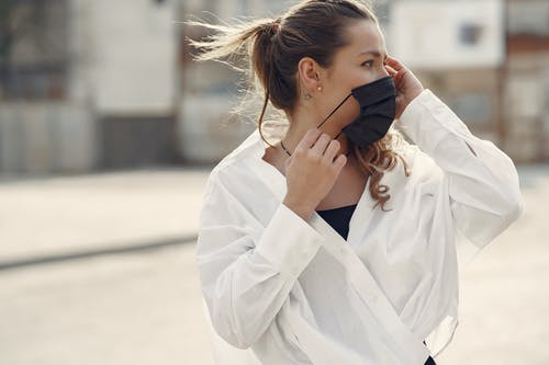 Woman in White Coat Holding Her Face