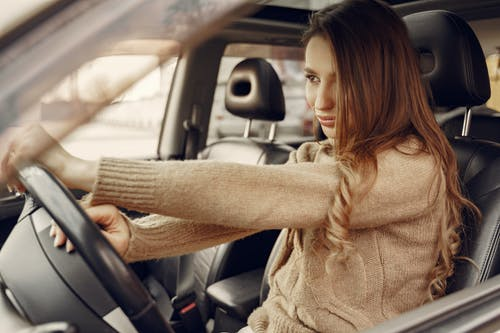 Woman in Beige Knit Sweater Driving Car