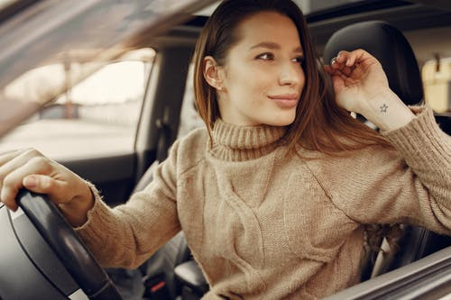 Smiling woman in driving seat of modern car