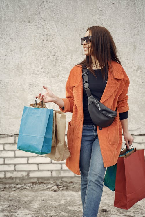 Fashionable female walking along pavement with purchases