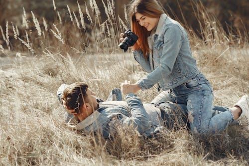 Woman in Blue Denim Jacket Holding Black Dslr Camera