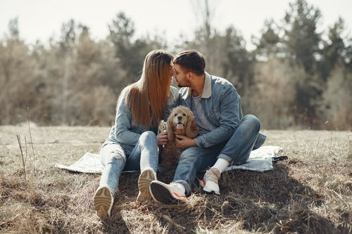 Loving couple having rest with dog on lawn