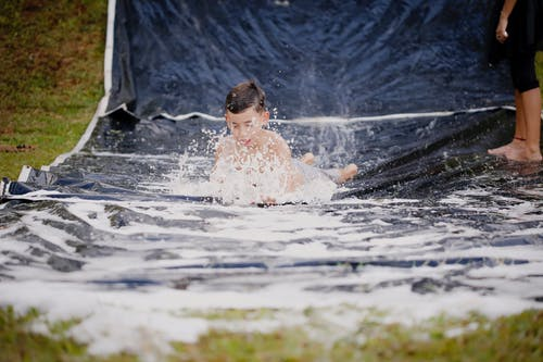Boy Playing On A Slip And Slide