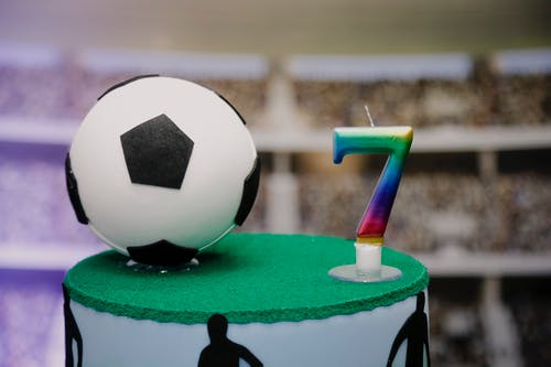 Delicious birthday cake with football theme and number candle