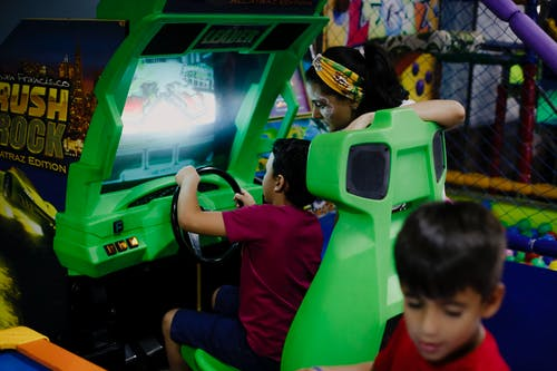 Anonymous boy playing car racing simulator near mother and sibling