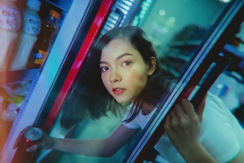 Calm ethnic woman taking refreshing drink from refrigerator in shop