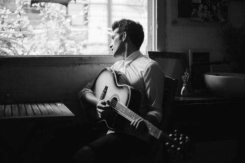 Man Playing Guitar In Grayscale Photography