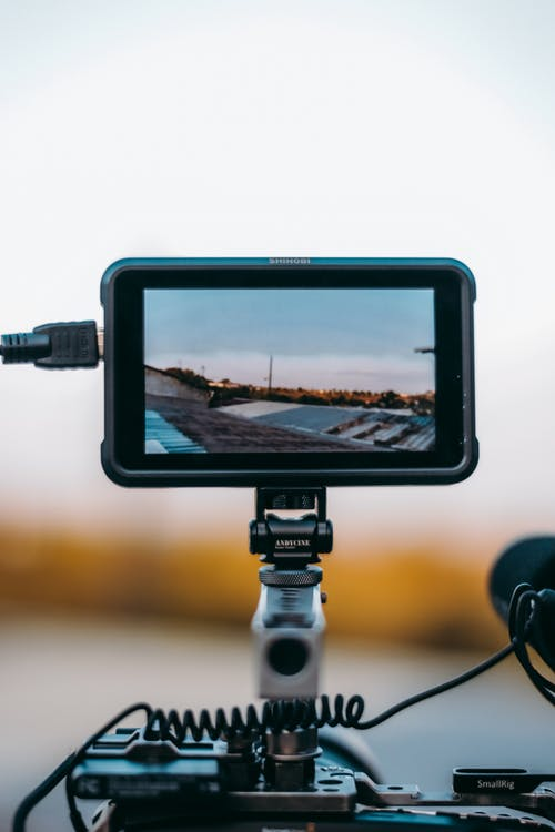 Contemporary rectangular shaped video camera monitor with charger and display showing pictures of roofs of houses in city under blue sky on tripod