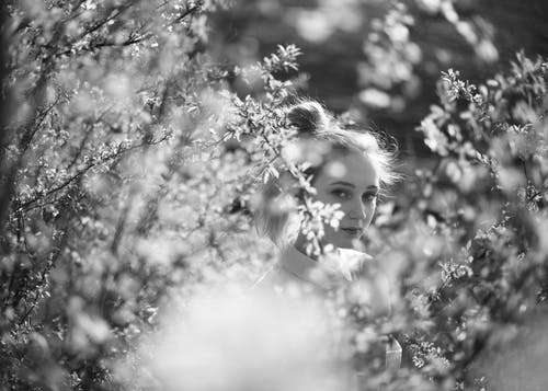 Grayscale Photo Of Woman near Plants