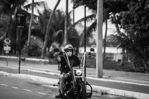 Grayscale Photo of Man and Woman Riding Motorcycle