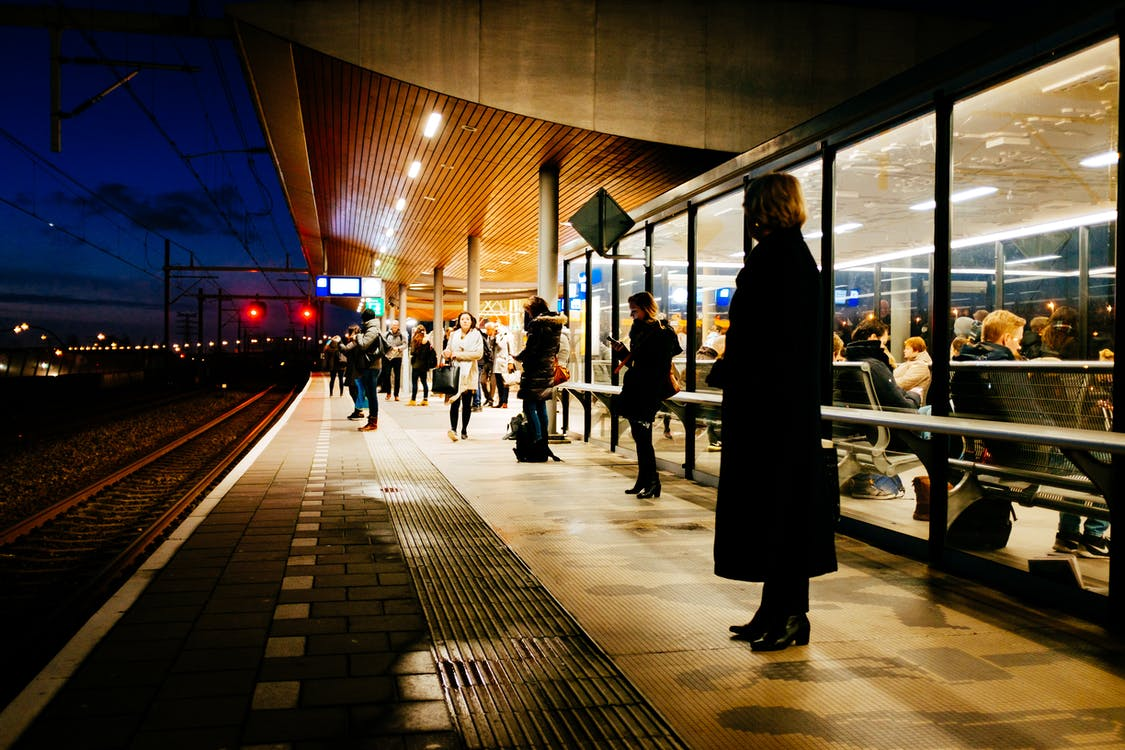 People Waiting on Train Station Platform at Night