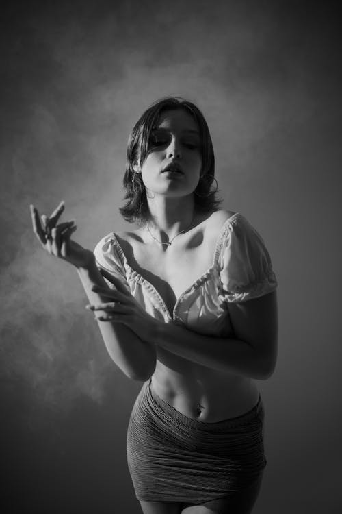Grayscale Photo of Woman in White Crop Top and Skirt