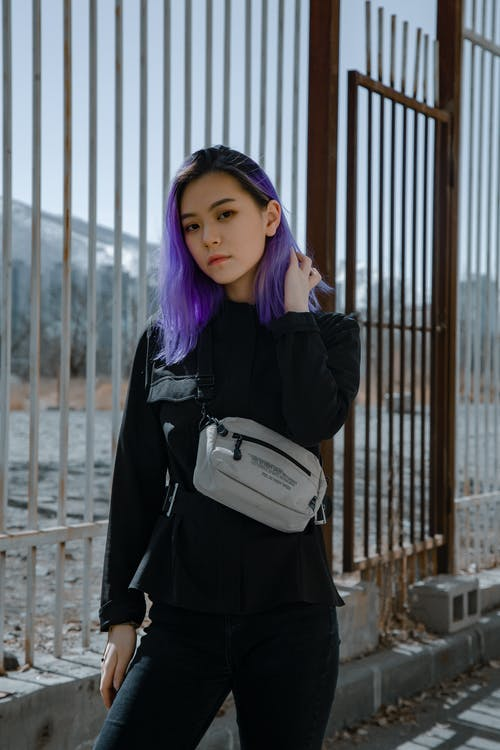 Woman in Black Jacket Holding White Leather Sling Bag