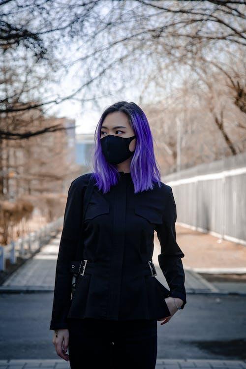 Woman in Black Dress Standing on Sidewalk