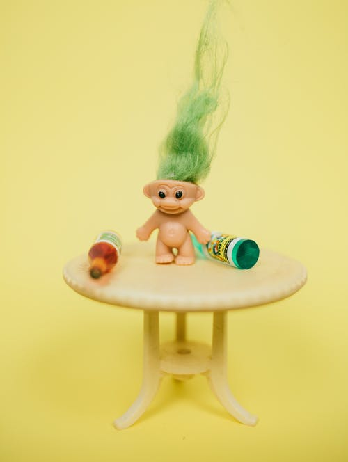 Mini troll toy on table with bottles