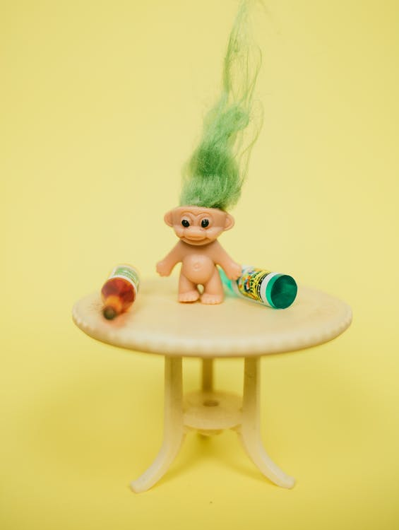 Funny troll toy with green hair placed on table miniature with various bottles against yellow background