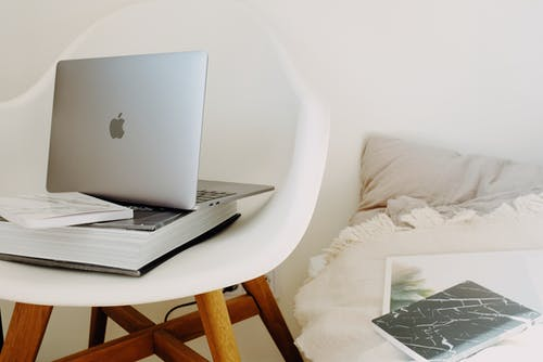 Modern laptop placed on book on armchair near bed in bedroom