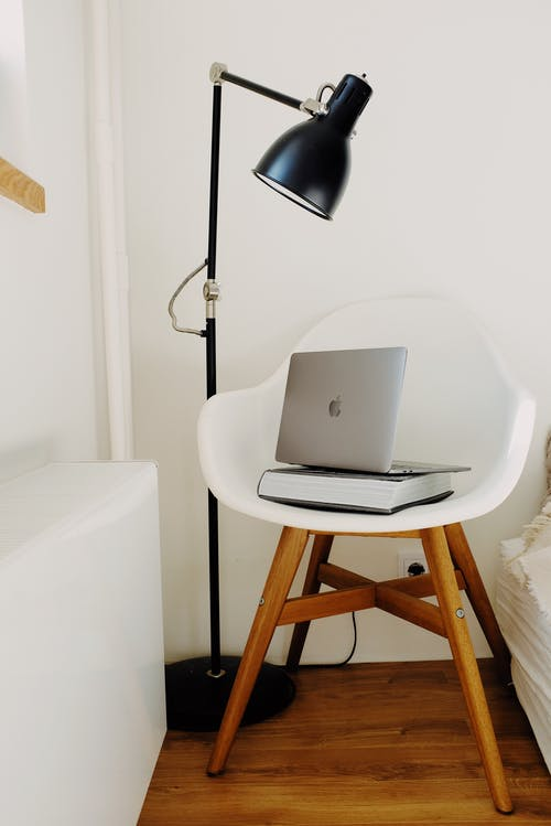 Portable laptop with book on white armchair at white wall with black floor lamp in modern light bedromo