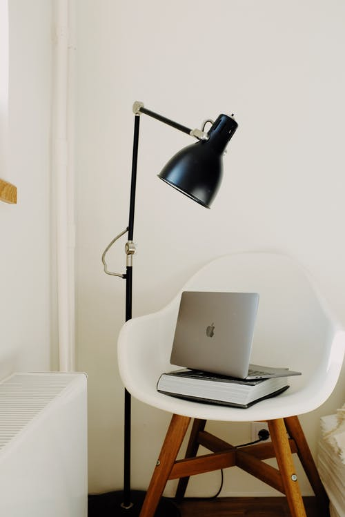Stylish workplace with laptop and book on white chair near floor lamp near wall in light modern apartment