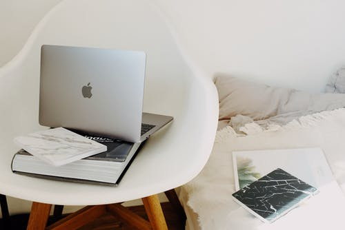 Portable laptop placed on book on white chair near bed in room