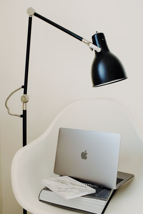 Laptop placed on black book on white armchair under lamp near wall in room