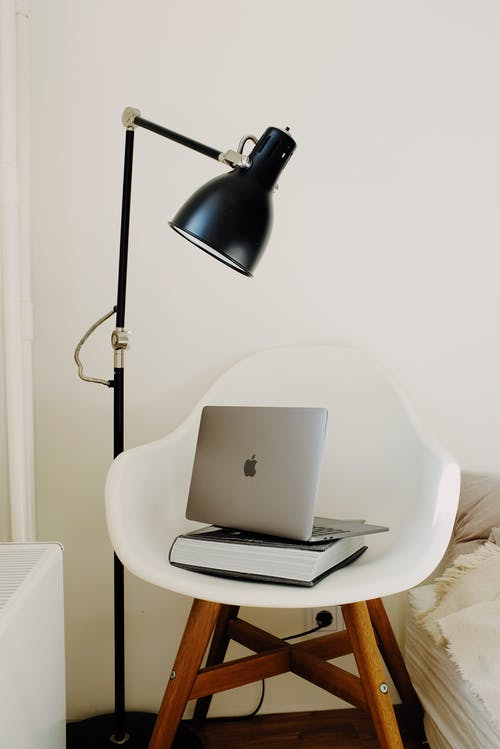 Laptop on Top of a Book on White Chair