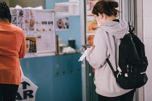 Woman in Gray Hoodie Standing Waiting in Line