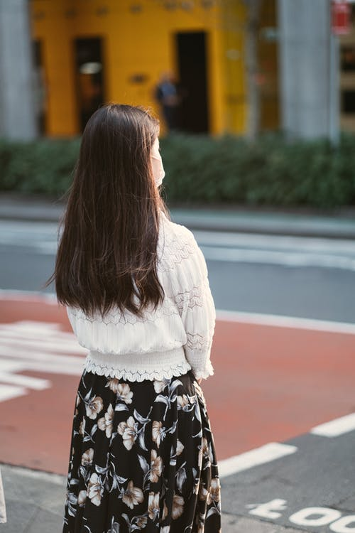 Woman in White Long Sleeve Shirt and Black and White Floral Skirt Standing on Sidewalk