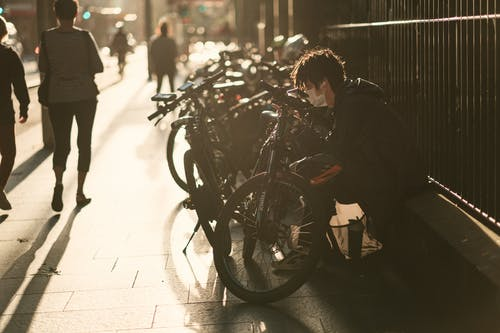 Man in Black Jacket In Front of Bicycle