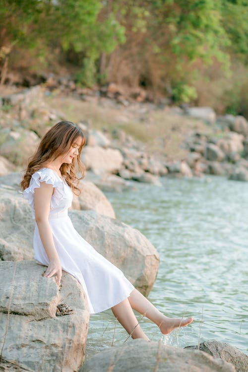 Woman in White Dress Sitting on Rock Near Body of Water