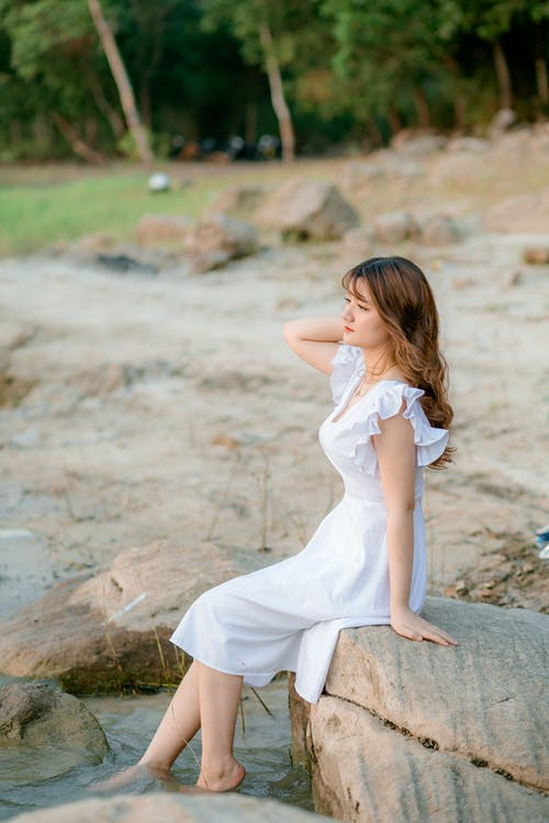 Girl in White Dress Sitting on Rocks