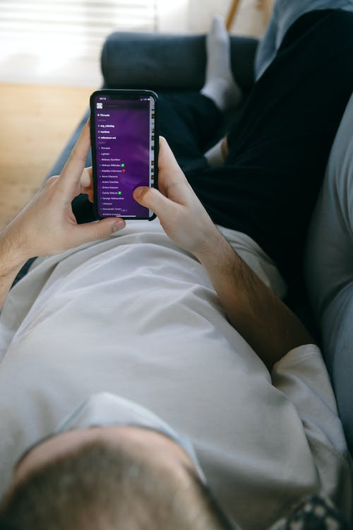 Man Lying Down Holding His Smartphone