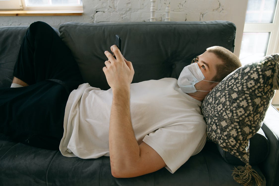 Man Lying Down Holding His Mobile Phone
